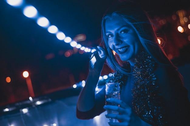 Mujer sonriente con una copa de champán y lámparas azules