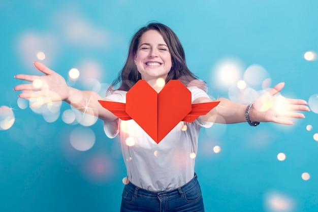 Mujer sonriente y corazón con alas