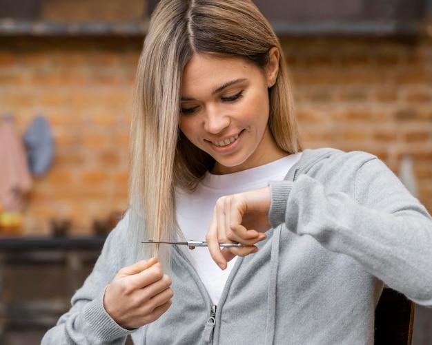 Mujer sonriente cortando su propio cabello
