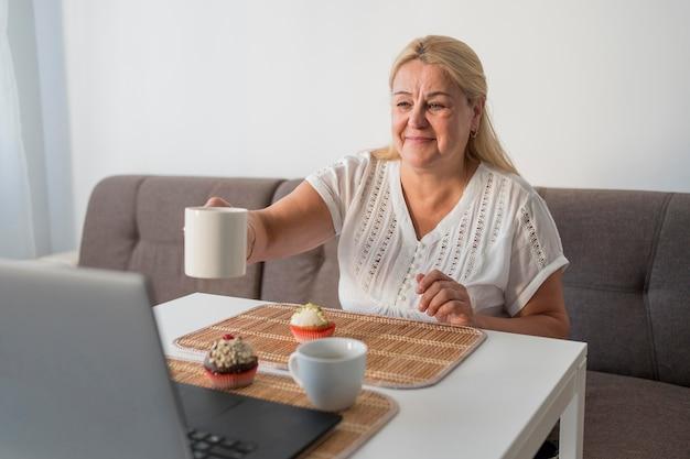 Mujer sonriente en cuarentena tomando café con amigos en la computadora portátil