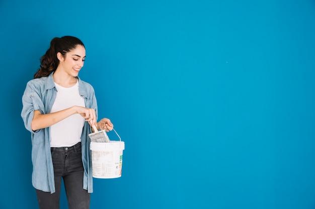 Mujer sonriente con cubo de pintura