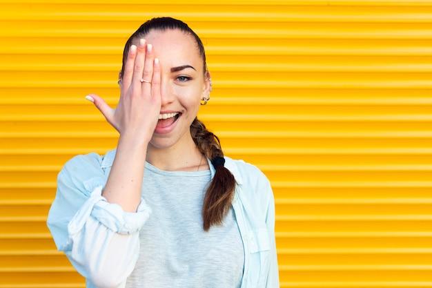 Mujer sonriente cubriendo un ojo