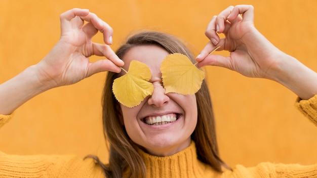 Mujer sonriente cubriendo sus ojos con hojas amarillas