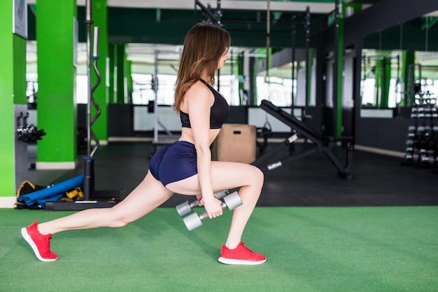 Mujer sonriente con cuerpo en forma fuerte está haciendo diferentes ejercicios en el moderno club deportivo con espejos