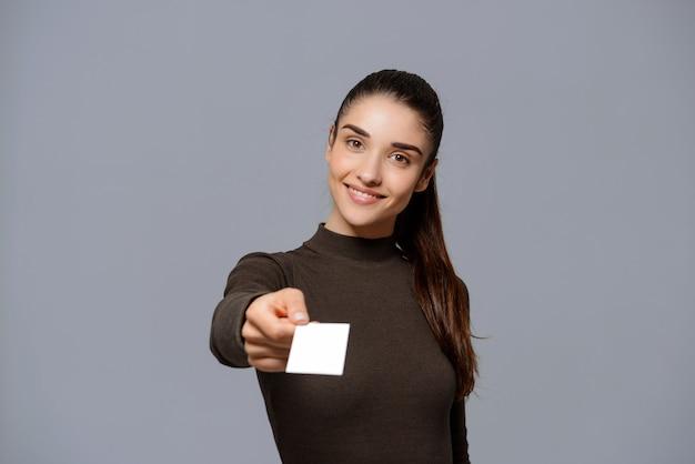 La mujer sonriente le da su tarjeta de visita