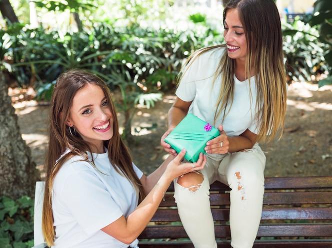 Mujer sonriente dando un regalo a su amigo en el parque