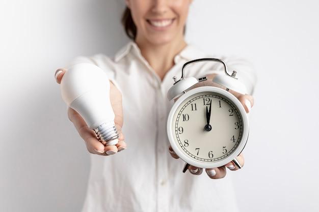 Mujer sonriente defocused con bombilla y reloj