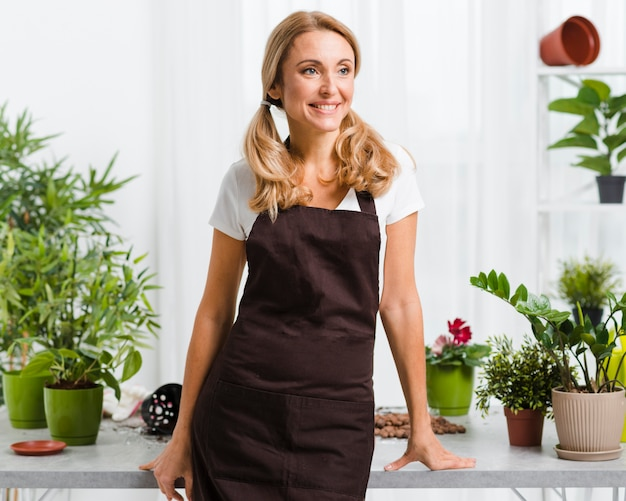 Mujer sonriente con delantal en invernadero