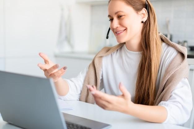 Mujer sonriente delante del monitor de la computadora portátil durante la conversación en línea. trabajo remoto. videollamada online.