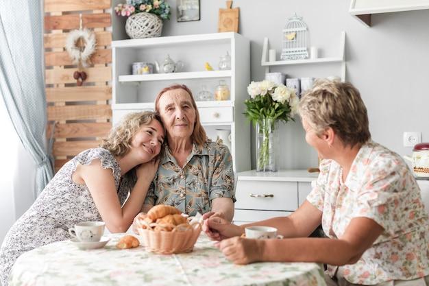 Mujer sonriente desayunando con su madre y su abuela en casa