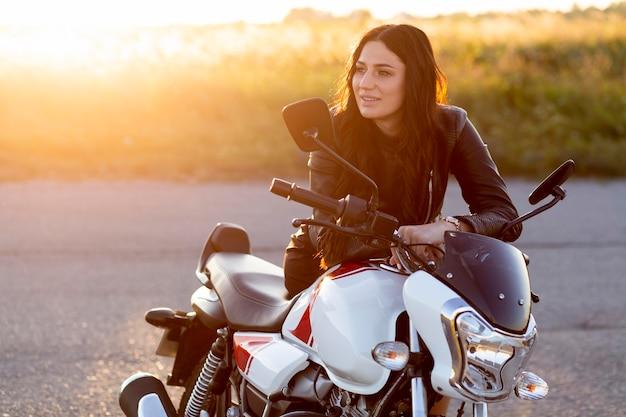Mujer sonriente descansando sobre su motocicleta en la puesta de sol