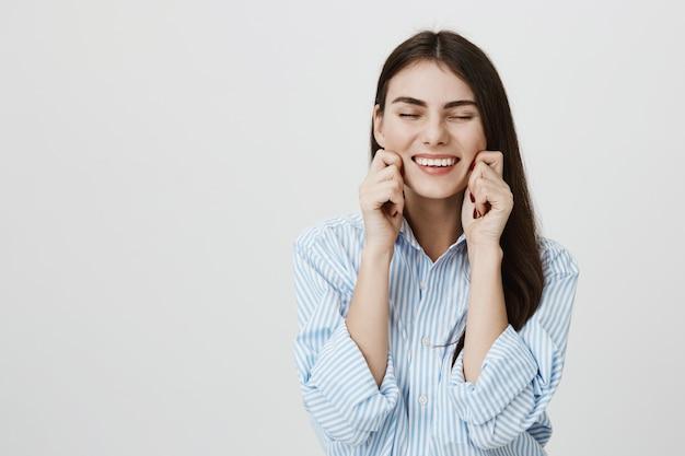 Mujer sonriente despreocupada tirando de sus propias mejillas y riendo