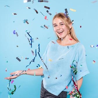 Mujer sonriente disfrutando de tiempo de confeti