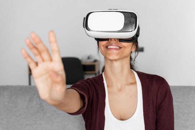 Mujer sonriente divirtiéndose en casa con casco de realidad virtual