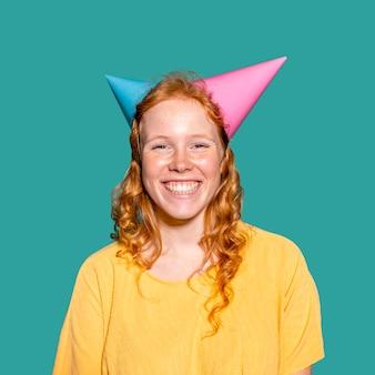 Mujer sonriente con dos conos de cumpleaños