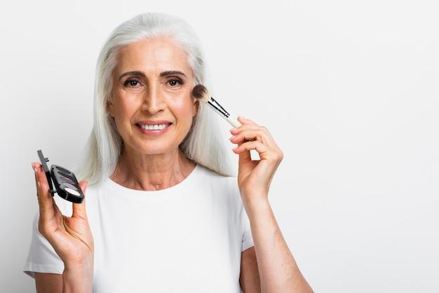 Mujer sonriente con elementos de maquillaje