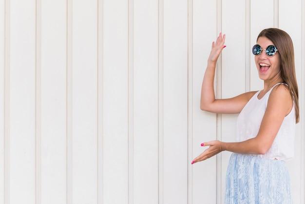 Mujer sonriente emocionada que señala por las manos en espacio vacío