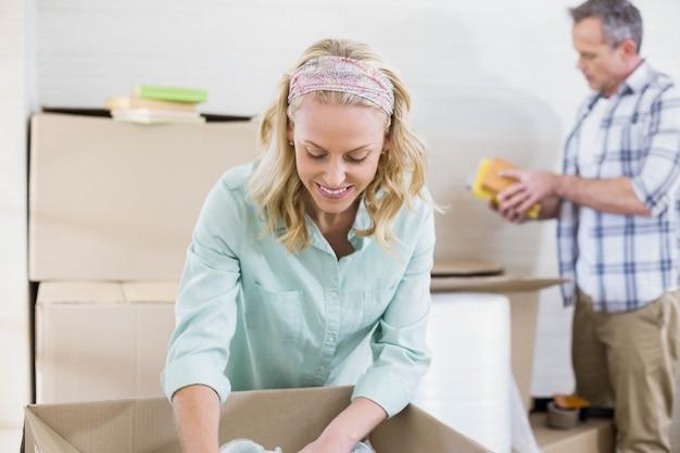 Mujer sonriente empacando una taza en una caja con su esposo detrás de ella
