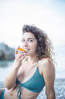 Mujer sonriente en bikini sentada en la playa aplicando bálsamo en los labios