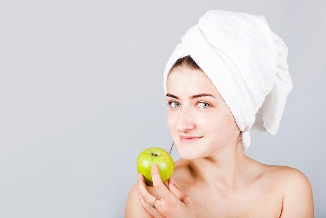 Mujer sonriente en toalla con manzana