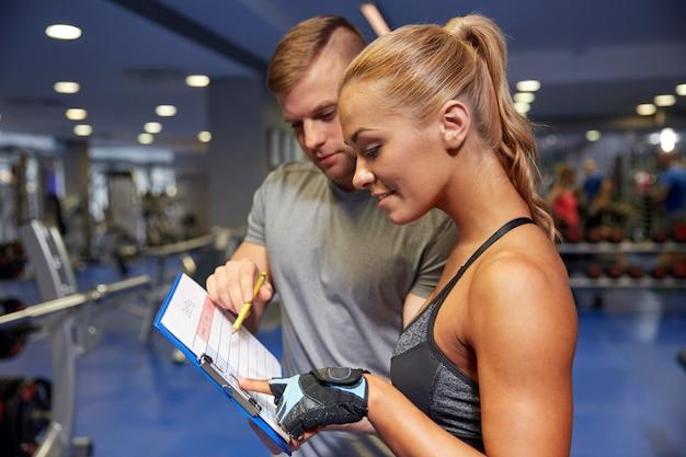 Mujer sonriente con entrenador y portapapeles en gimnasio