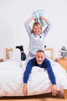 Mujer sonriente envejecida con almohada y hombre acostado en cama