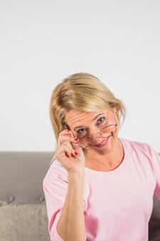 Mujer sonriente envejecida en blusa y lentes color de rosa en el sofá