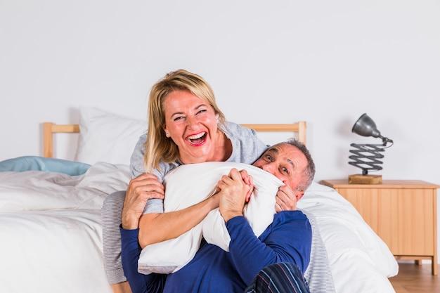 Mujer sonriente envejecida que abraza al hombre y que se divierte con la almohada cerca de cama