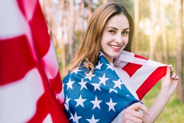 Mujer sonriente envuelta en bandera nacional americana