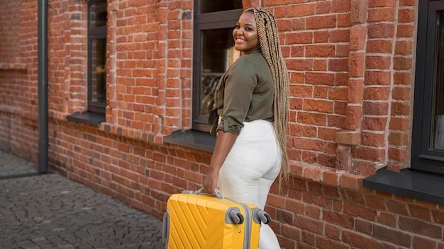 Mujer sonriente con equipaje amarillo caminando