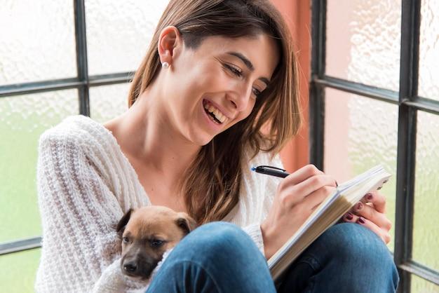 Mujer sonriente escribiendo en el cuaderno