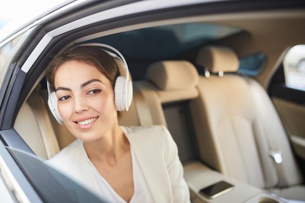 Mujer sonriente escuchando música en coche
