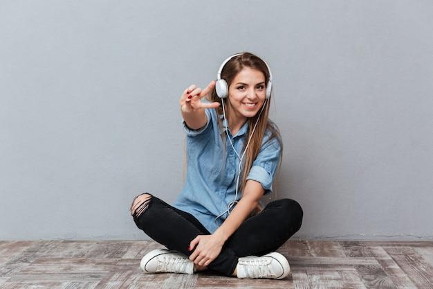 Mujer sonriente escuchando música en el piso
