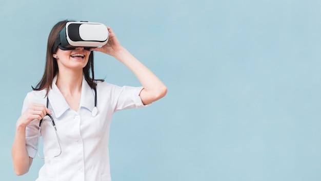 Mujer sonriente con estetoscopio con casco de realidad virtual