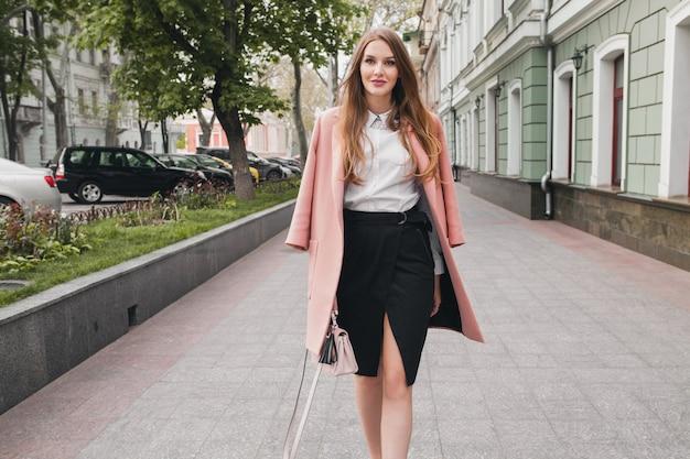 Mujer sonriente con estilo atractivo caminando calle de la ciudad en abrigo rosa