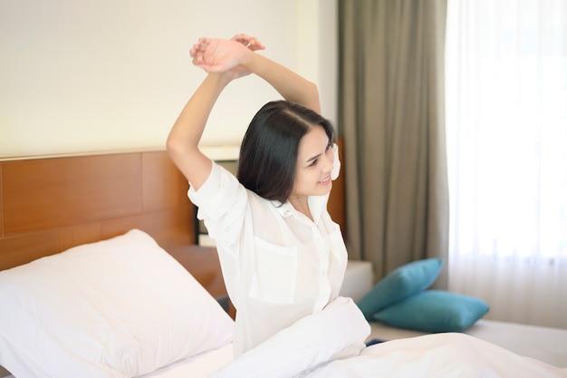 Una mujer sonriente estirando sus manos después de despertarse por la mañana en casa.