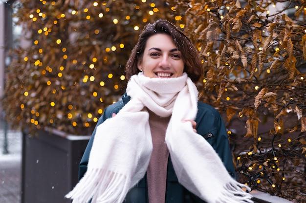 Mujer sonriente feliz caucásica disfrutando de la nieve y el invierno, vistiendo bufanda caliente Foto gratis