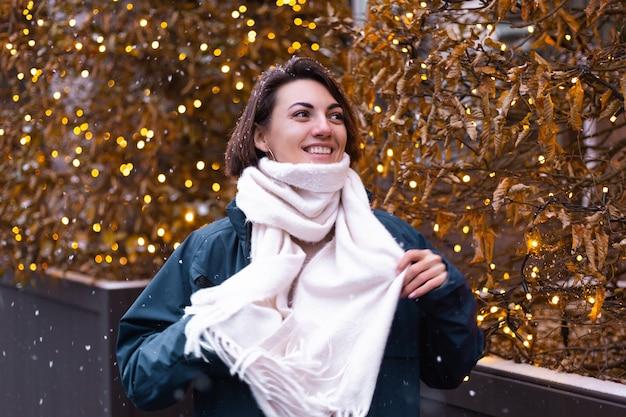 Mujer sonriente feliz caucásica disfrutando de la nieve y el invierno, vistiendo bufanda caliente