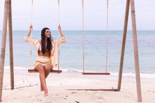 Mujer sonriente feliz en columpio en la playa, luz cálida del día.
