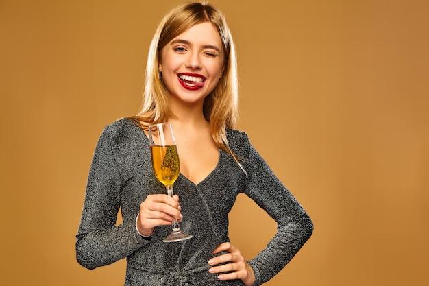 Mujer sonriente feliz en elegante vestido glamoroso con copa de champán.