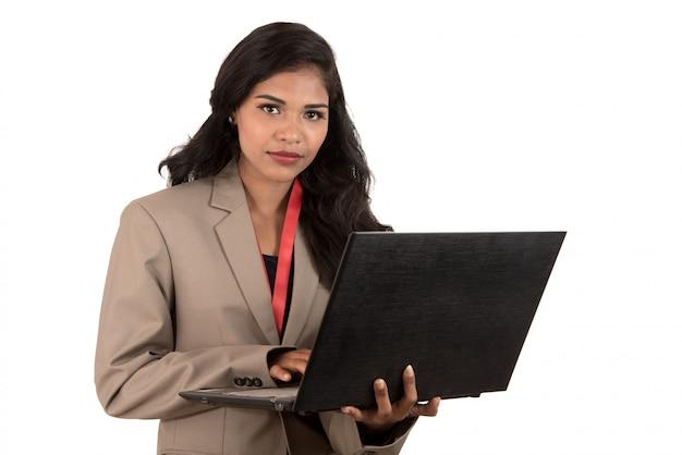 Mujer sonriente feliz joven que sostiene el ordenador portátil.