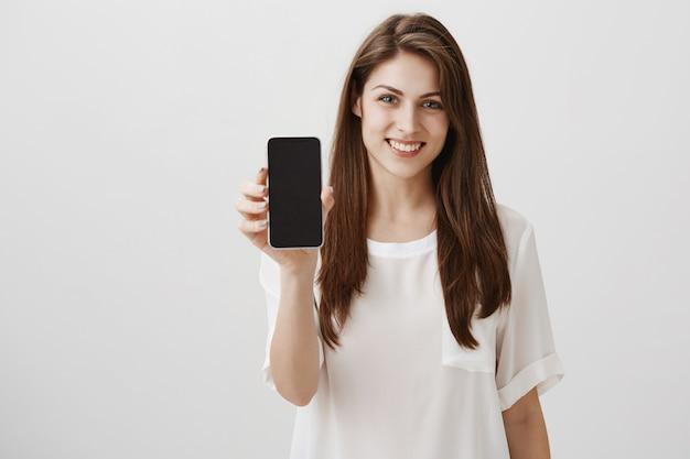 Mujer sonriente feliz que muestra la pantalla del móvil, recomienda la aplicación o el sitio de compras