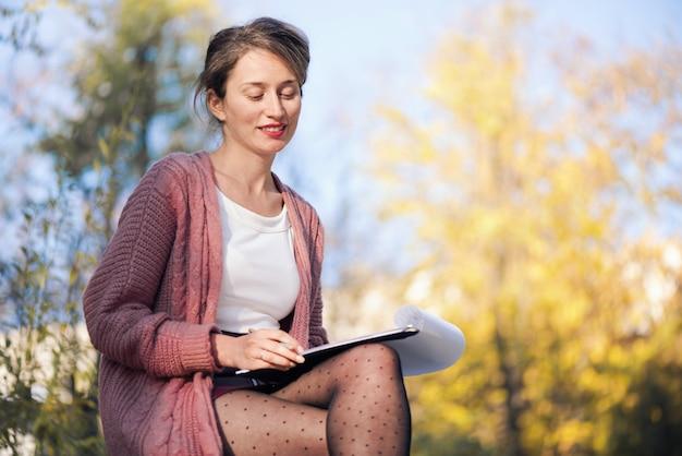 Mujer sonriente feliz trabajando con papeles y escribiendo cartas