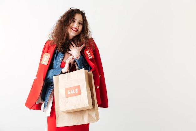 Mujer sonriente feliz de la venta que sostiene bolsos de compras