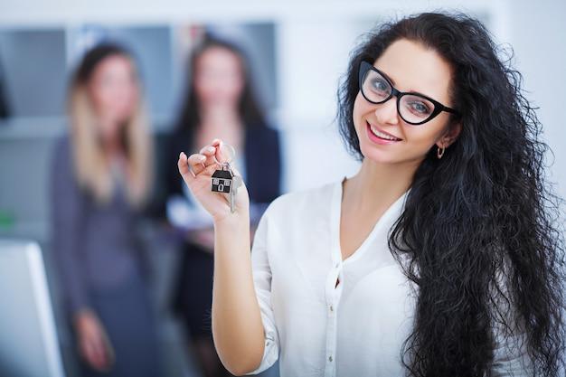 Mujer sonriente firmando documentos en el banco con el agente