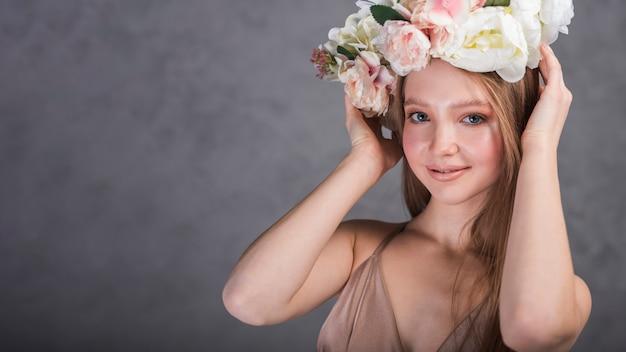Mujer sonriente con flores en la cabeza