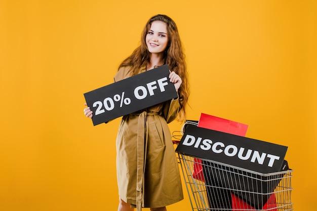 Mujer sonriente en gabardina con signo de descuento del 20% y coloridas bolsas de compras en carro aislado sobre amarillo