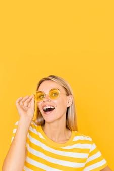 Mujer sonriente con gafas amarillas