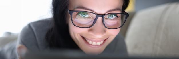 Mujer sonriente con gafas se encuentra en el sofá y tiene un concepto de tiempo ilimitado de internet de tableta