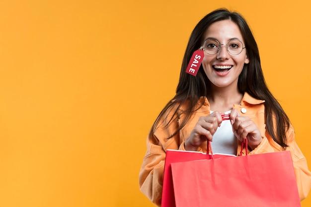 Mujer sonriente con gafas con etiqueta y sosteniendo la bolsa de compras